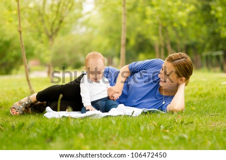Mother and baby lying on the grass in park