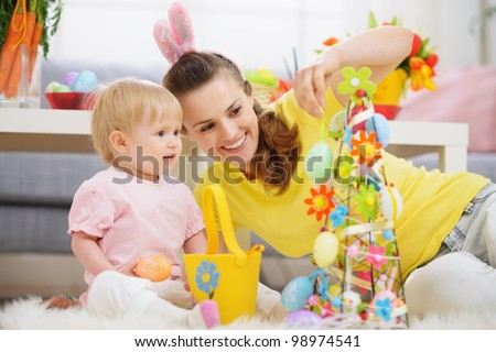 Mother and baby making Easter decoration