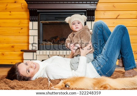 Mother and baby playing and smiling. Happy family.Home interior. Winter season. #322248359