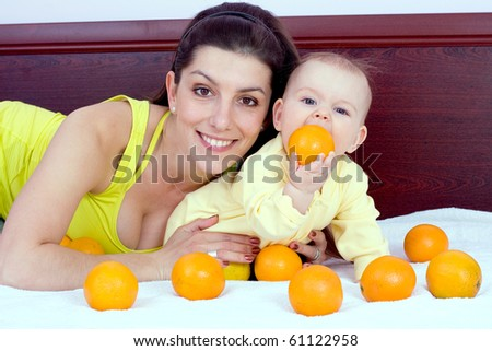 Mother and baby plays with oranges fruits