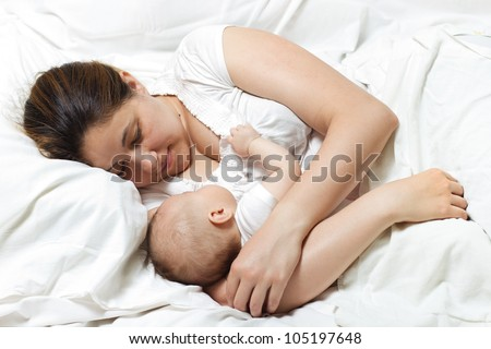 Mother and baby relaxing in bed.