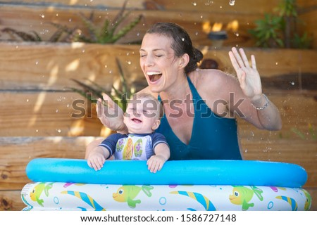 Mother And Baby Son Playing In Outdoor Paddling Pool Together