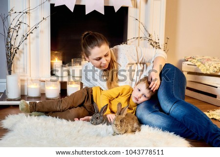 Mother and baby son playing with a rabbit. Mom and son lying cozily in a warm room with a candled fireplace and cute rabbits #1043778511
