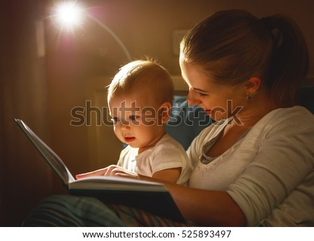 mother and baby sonreading a book in bed before going to sleep