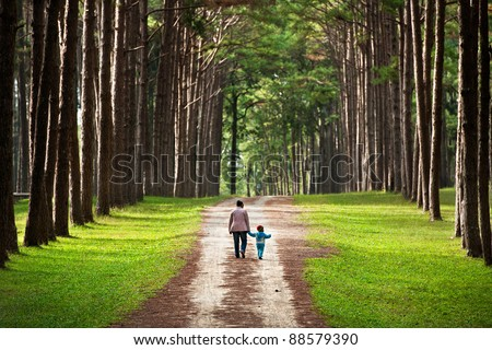 Mother and baby walk on country rural road in pine forest