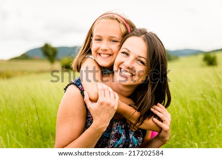 Mother and child are hugging and having fun outdoor in nature