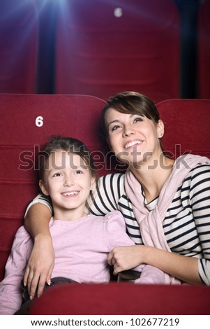 Mother and child are watching a movie at the cinema