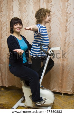 Mother and child, boy of eight years (European) on gum bicycle trainer at home.