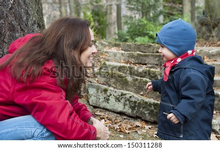 Mother and child, boy or girl, facing each other and smiling in an autumn park.