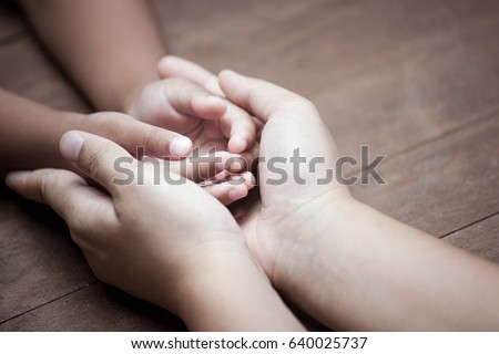 Mother and child daughter holding hand together with love in vintage color tone