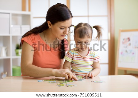 Mother and child daughter playing at home. Woman and kid assembling Jigsaw Puzzle #751005511
