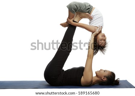 Mother and child doing yoga together in a fitness studio