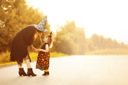 Mother and child dressed in halloween witch costumes. copycspace, empty space for text, greeting card. happy halloween.