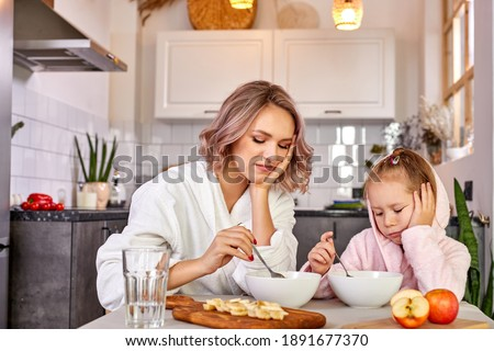 Photo of  mother and child girl sit dont' want to eat in the morning, they have no appetite, want to sleep. in the kitchen