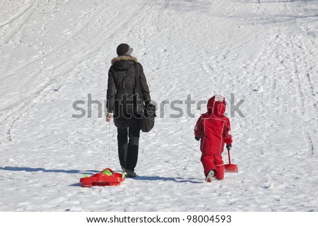 Mother and child going to slide from hill