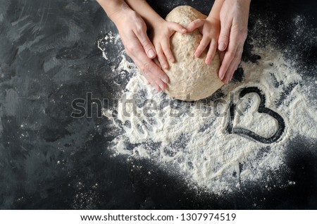 Mother and child hands prepares the dough with flour on dark wooden table. Bakery background. Heart painted on flour
