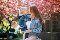 Mother and child hugging and kissing outdoors. Spring blooming sakura flower background. Family on a walk in nature. Happy mother's day. Happy family. Fashion, family and holidays.