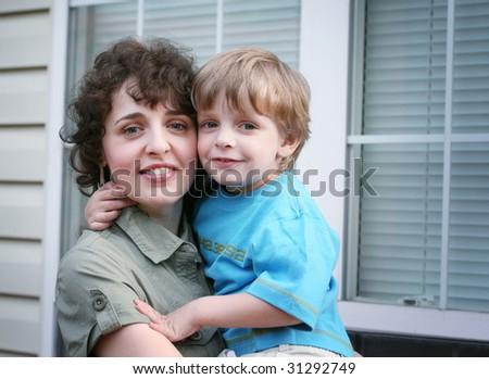 Mother and child in front of house window