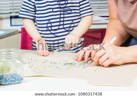 Mother and child make a pattern of beads on the fabric. Workplace for handicraft creativity. #1080317438