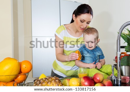 Mother and child making fresh orange juice -healthy life
