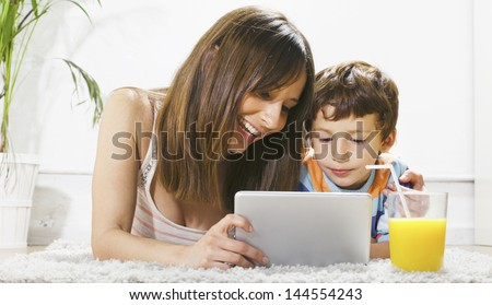 Mother and child on a carpet stretched with pad and orange juice./ Mother and son having fun with a digital tablet in home