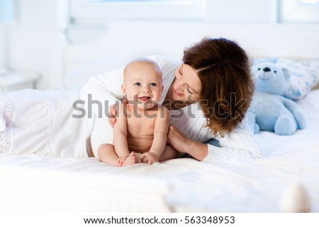 Mother and child on a white bed. Mom and baby boy in diaper playing in sunny bedroom. Parent and little kid relaxing at home. Family having fun together. Bedding and textile for infant nursery