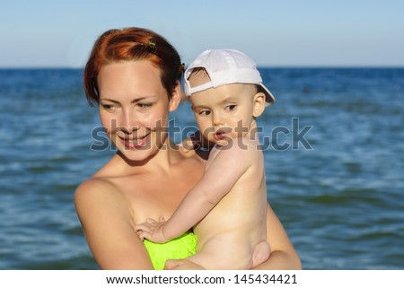 Mother and child on the beach in the sea