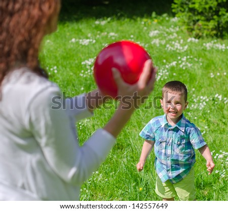 Mother and child playing with the ball outdoors