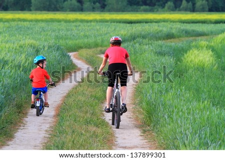 Mother and child riding bikes together on a green field