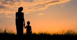 Mother and child silhouette walking in a field at sunset.