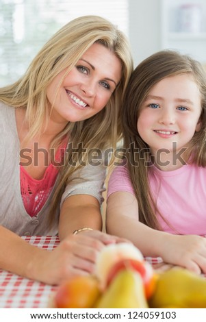 Mother and child sitting at kitchen table smiling with fruit bowl on table