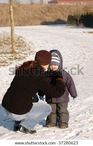 Mother and child walk on a winter road.
