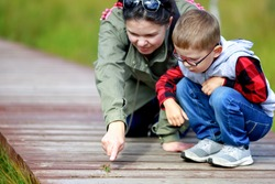 Mother and child walking in nature. The woman points her finger at a beetle - a large green grasshopper. The kid wears glasses.