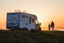 mother and child watching a sunset over the sea, traveling in the motor home