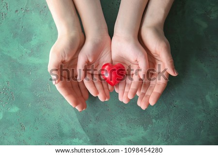 Mother and child with red heart on color background. Health care concept