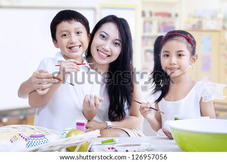 Mother and children are painting in a classroom