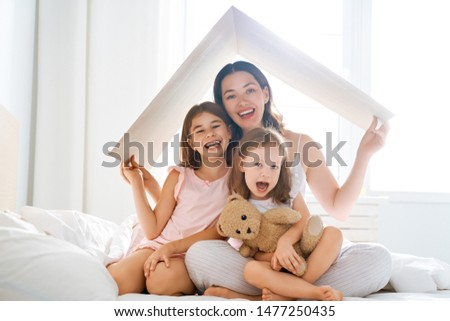 Mother and children girls in the room with a symbol of roof. Concept of housing for young family.