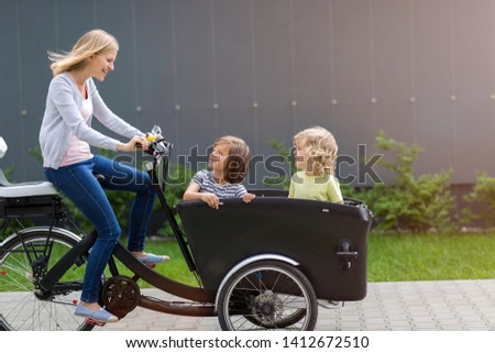 Mother and children having a ride with cargo bike stock photo