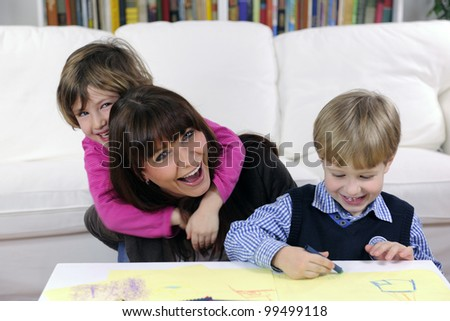 Mother and children having fun at home in living room