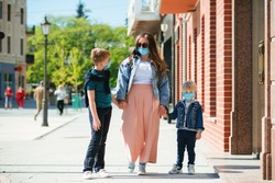 Mother and children in safety masks walking city street. Family wearing face masks outdoors. Coronavirus outbreak. Medical masks to prevention coronavirus. New real life 2020. Lifestyle, travel.