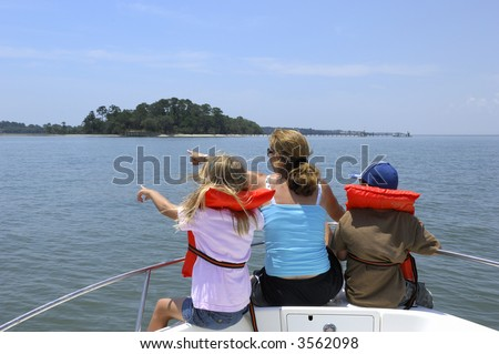 Mother and children on boat looking left. - stock photo