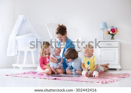Mother and children play indoors. Family with kids in a white bedroom. Mom with baby, boy and girl playing and reading books at home. Beautiful nursery for baby and toddler. Room for preschool child.