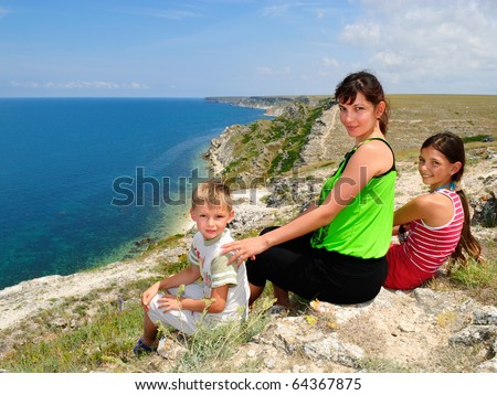 Mother and children sitting on the edge of a cliff at the seaside - stock photo