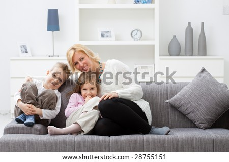 Mother and children sitting together on couch at living room. #28755151