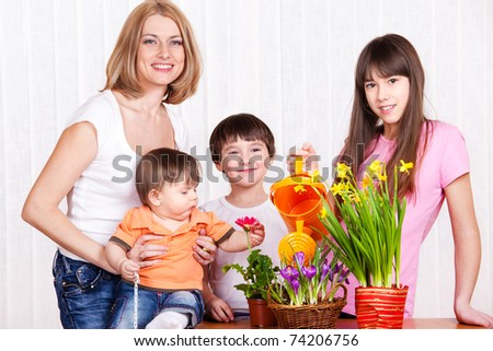 Mother and children watering flowers