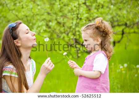 Mother and curly girl blowing dandelion away - stock photo