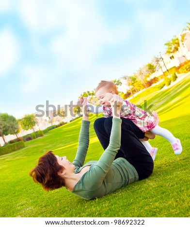 Mother and cute baby daughter playing outside at summer backyard, young woman with little girl, female holding child, beautiful mommy and cute kid lying on the grass, happy family in nature concept - stock photo