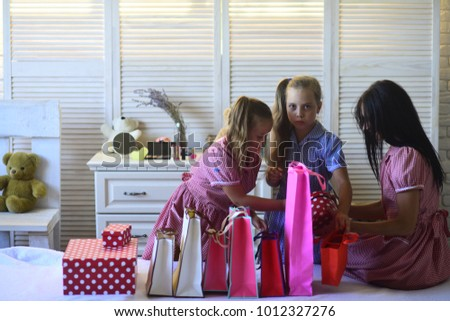 Mother and cute daughters with shopping bags and packs. Woman and children wearing stylish dresses open gifts at home. Family with cheerful faces and presents. Family shopping and celebration concept. #1012327276