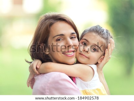 Mother and cute little daughter portrait outdoors.