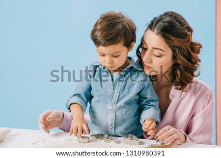 mother and cute little son cutting figures in dough with dough molds together on bicolor background